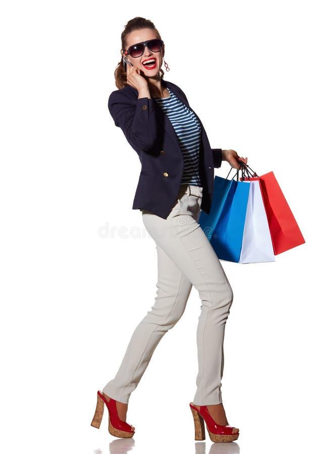 Mujer con la mujer de los panieres que habla en smartphone y caminar foto de archivo