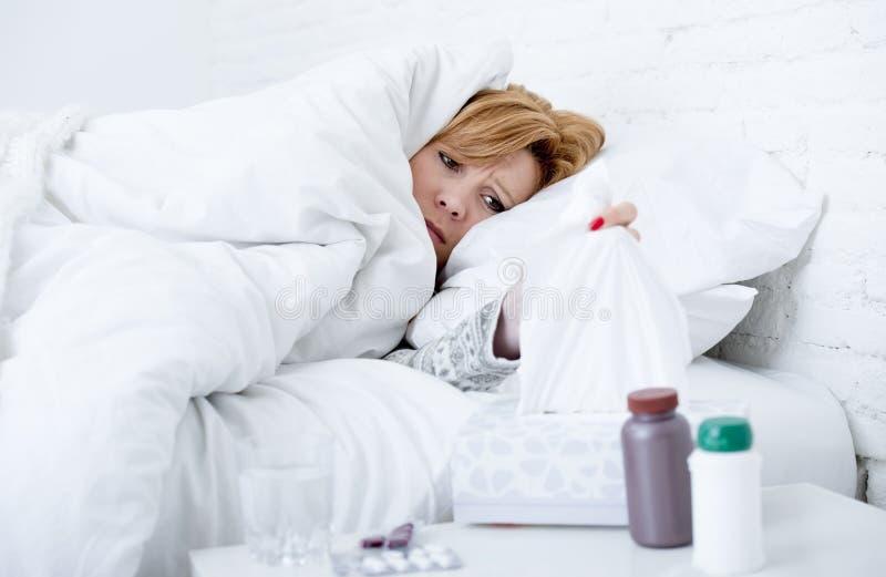 mujer con la nariz de estornudo usando tejido en la cama que sufre el virus frío de la gripe que tiene medicinas fotografía de archivo libre de regalías