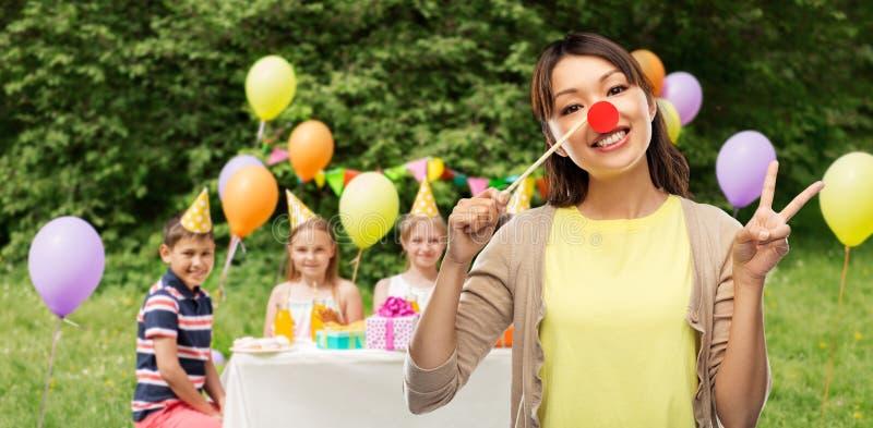 Mujer con la nariz del payaso en la fiesta del cumpleaños de los niños fotografía de archivo libre de regalías