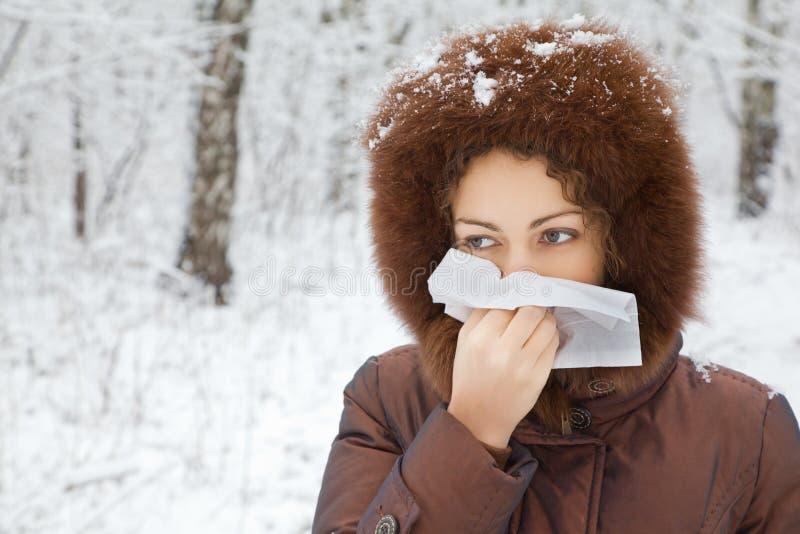 Mujer con la nariz que sopla de la bufanda en madera en invierno imagen de archivo