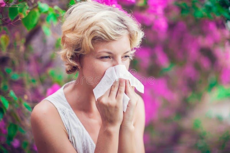 Mujer con la nariz que sopla del síntoma de la alergia fotos de archivo