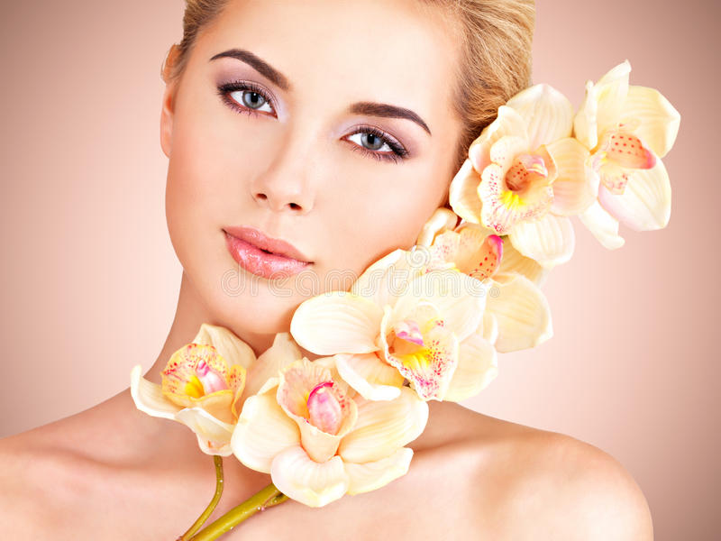 Mujer con la piel de la salud y flores en la cara fotografía de archivo libre de regalías