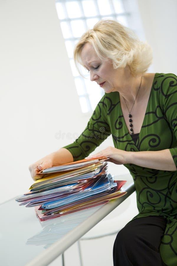 Mujer con la pila de papeleo fotos de archivo