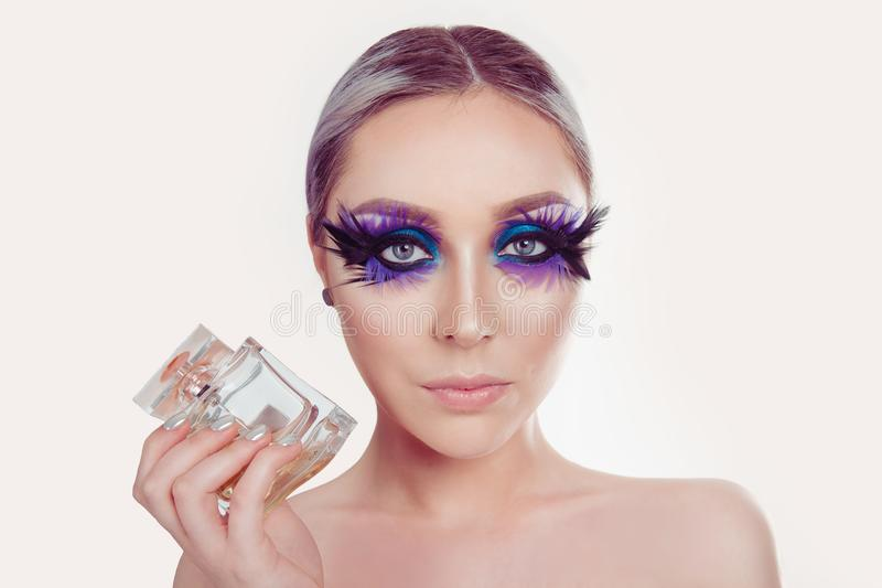 Mujer con la pluma púrpura artística del maquillaje de los ojos azules en las pestañas que celebran mostrar a perfume la joyería  foto de archivo