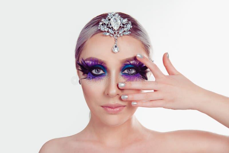 Mujer con la pluma púrpura artística del maquillaje de los ojos azules en las pestañas que sostienen la joyería de plata en la ca fotografía de archivo libre de regalías