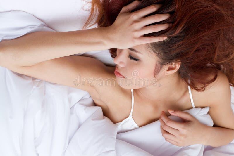 Mujer con la preocupación o la ansiedad en su cama, insomnio o sleeplessnes fotos de archivo