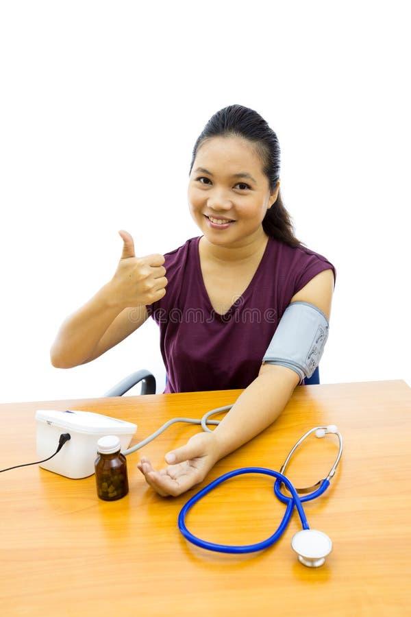 Mujer con la prueba de la presión arterial imagen de archivo