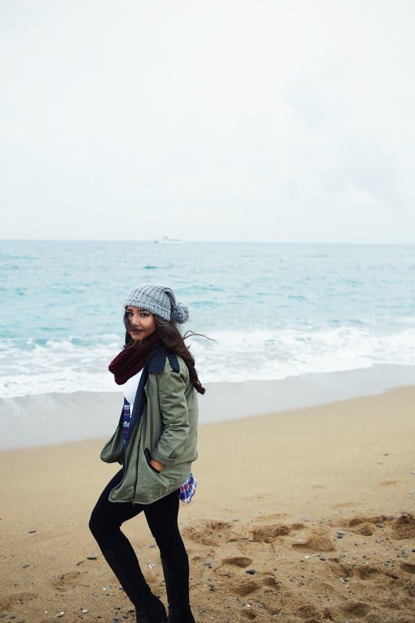 Mujer con la risa que coloca el mar cercano foto de archivo