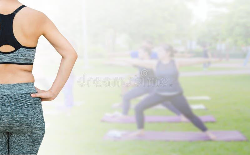 mujer con la ropa de deportes que lleva gorda del vientre que se prepara para el aislador de la yoga fotografía de archivo