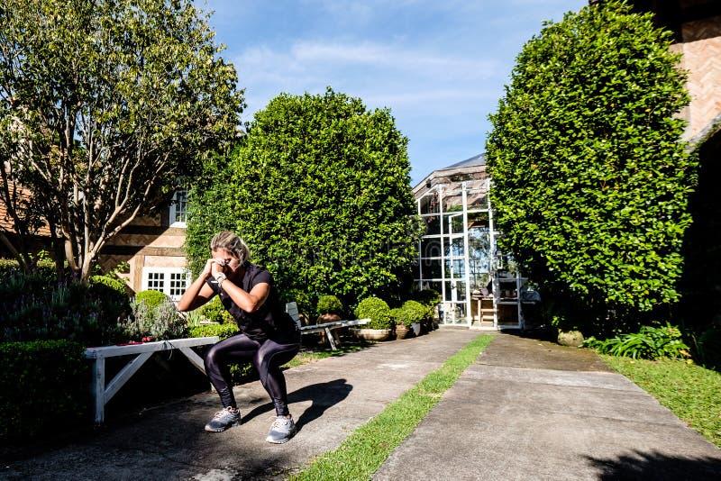 Mujer con la ropa negra que hace posiciones en cuclillas en el parque imágenes de archivo libres de regalías