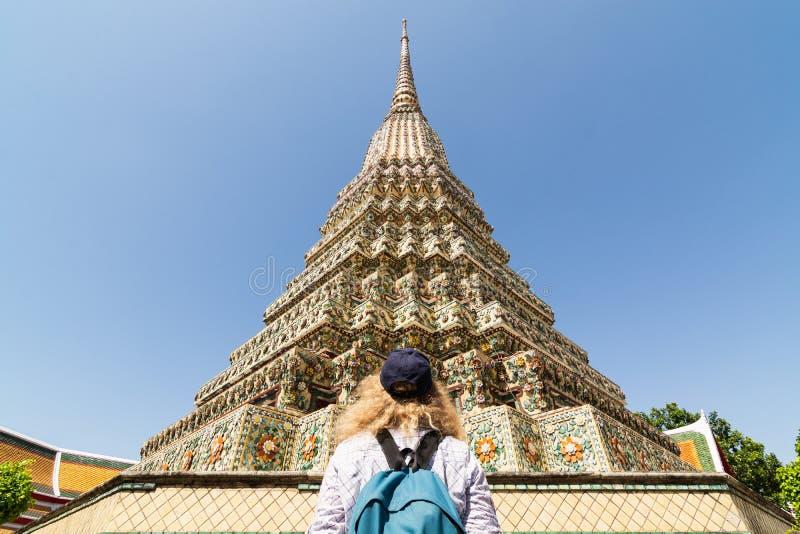 Mujer con la situación de la mochila delante del stupa gigante en el complejo del templo de Wat Pho Reclining Buddha en Bangkok, foto de archivo libre de regalías