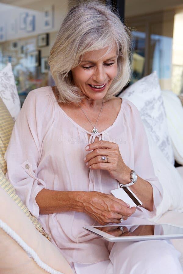 Mujer con la tableta de la tarjeta de crédito y de la pantalla táctil fotos de archivo libres de regalías