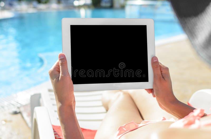 Mujer con la tableta en la piscina fotografía de archivo libre de regalías