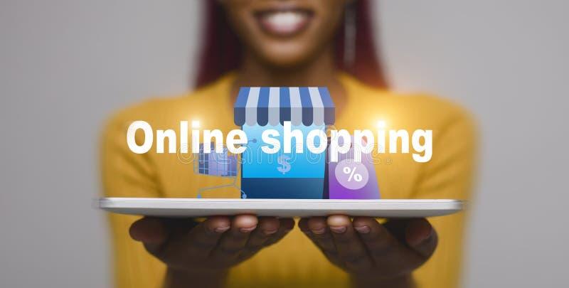 Mujer con la tableta que muestra concepto que hace compras en línea fotos de archivo