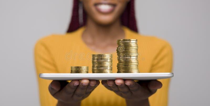 Mujer con la tableta que propone ganar el dinero en el Internrt imagenes de archivo