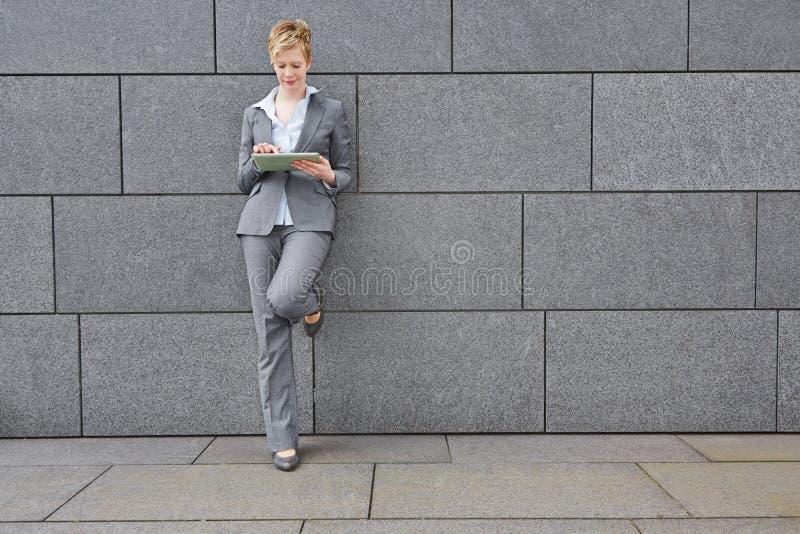 Mujer con la tableta que se inclina en la pared imagen de archivo