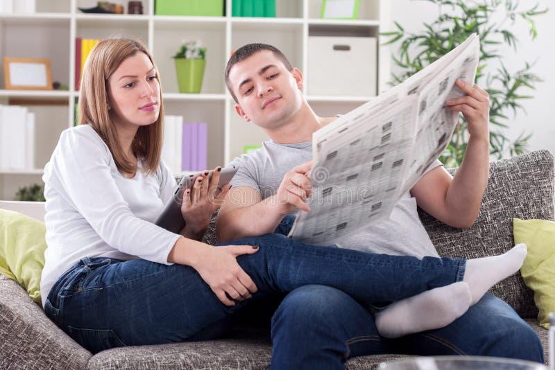 Mujer con la tableta y el marido con noticias de la lectura del periódico imagen de archivo