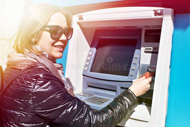 Mujer con la tarjeta de banco en la atmósfera fotos de archivo libres de regalías