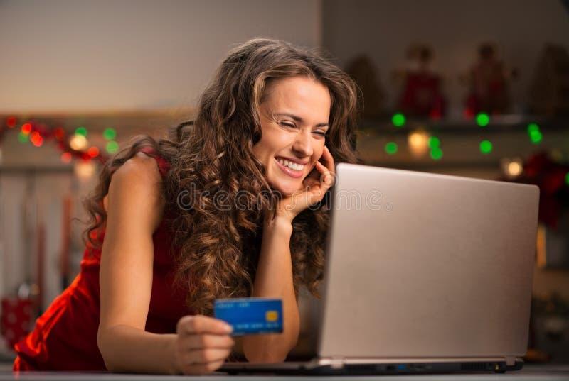 Mujer con la tarjeta de crédito que elige los regalos de la Navidad en el ordenador portátil fotografía de archivo