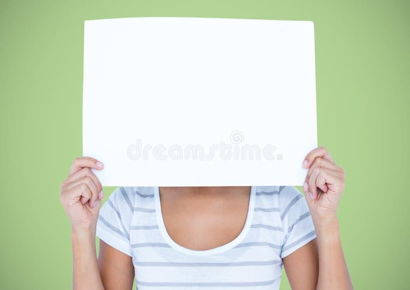 Mujer con la tarjeta en blanco grande sobre cara contra fondo verde imagen de archivo libre de regalías