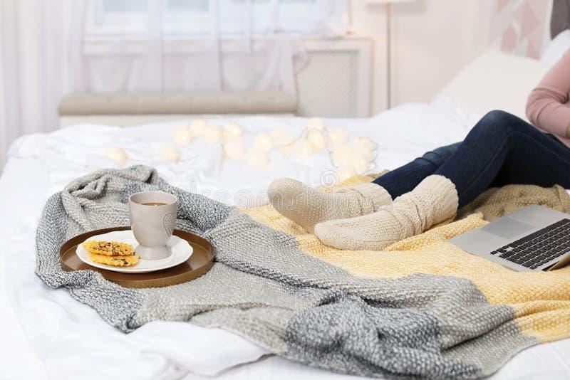 Mujer con la taza de bebida caliente y las obleas en cama en casa fotografía de archivo