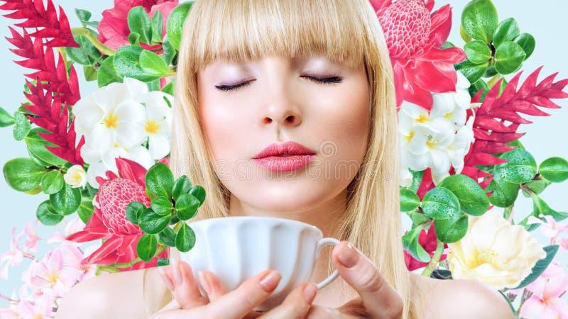 Mujer con la taza de bebida delante del fondo de las flores imagen de archivo