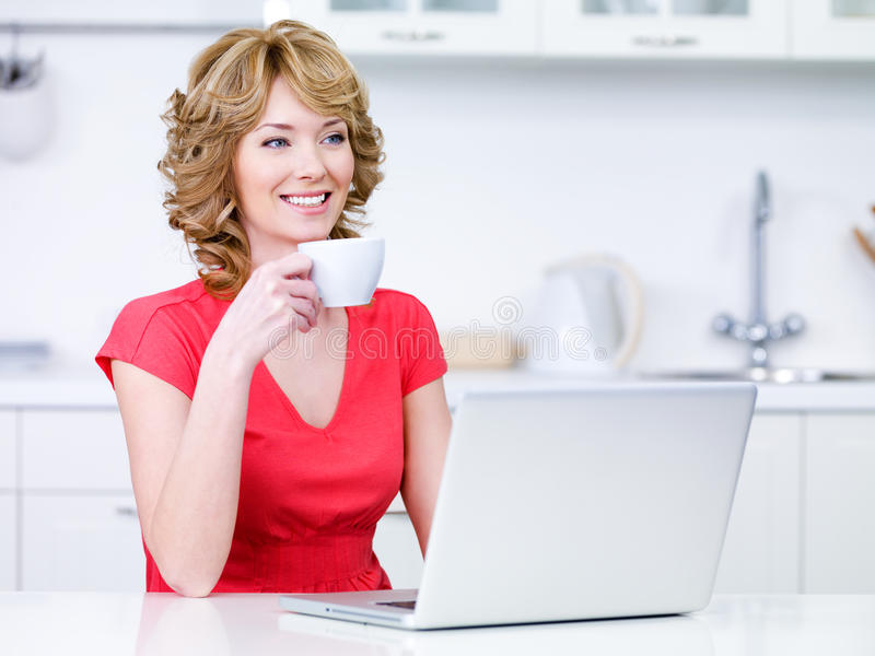 Mujer con la taza de café y de computadora portátil fotografía de archivo