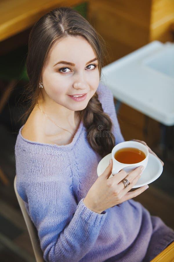 Mujer con la taza de té, pelo trenzado, vestido en suéter imagen de archivo