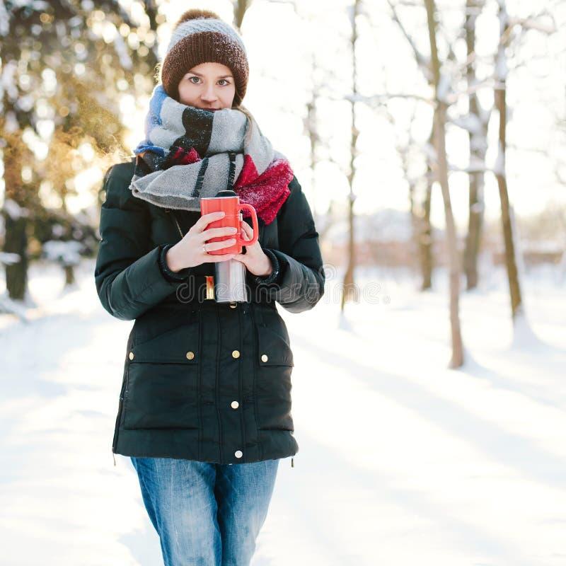 Mujer con la taza sus manos en invierno fotografía de archivo libre de regalías