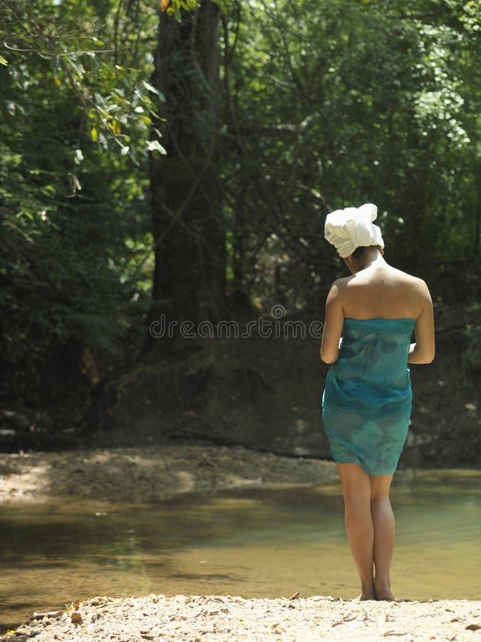 Mujer con la toalla envuelta en la cabeza y el cuerpo por el lago imágenes de archivo libres de regalías