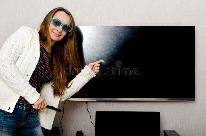 Mujer con la TV foto de archivo