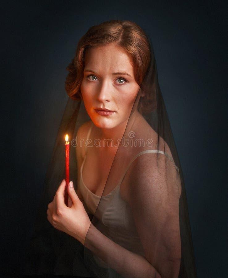 Mujer con la vela debajo del velo negro Foto de Halloween foto de archivo
