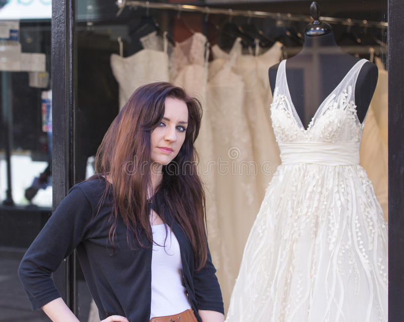 Mujer con la ventana de la tienda de ropa de la boda foto de archivo