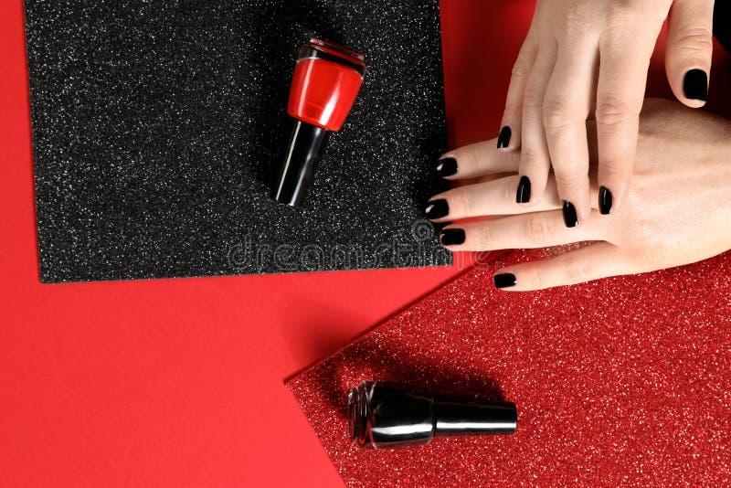 Mujer con las botellas negras de la manicura y del esmalte de u?as en fondo del color Espacio para el texto imagen de archivo