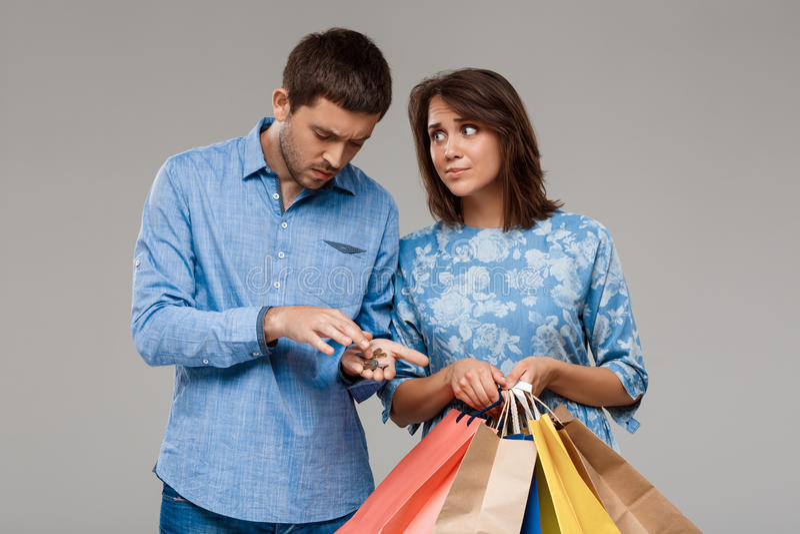 Mujer con las compras, hombre que sostiene el dinero pasado sobre fondo gris fotografía de archivo libre de regalías