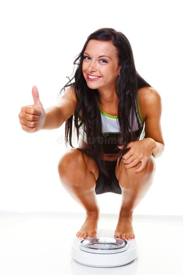 Mujer con las escalas después de una dieta acertada imagen de archivo libre de regalías
