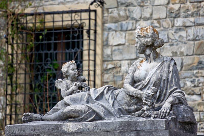 Mujer con las estatuas del ángel en el castillo de Peles, Rumania imagen de archivo libre de regalías