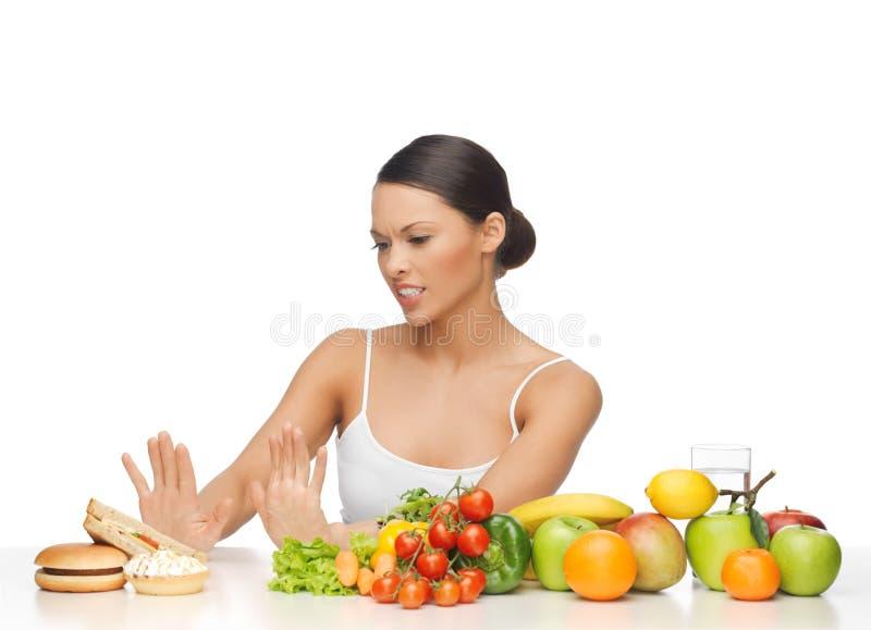 Mujer con las frutas que rechaza la hamburguesa imagen de archivo libre de regalías