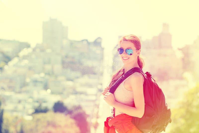 Mujer con las gafas de sol de la mochila que viajan en la ciudad de San Francisco imagenes de archivo