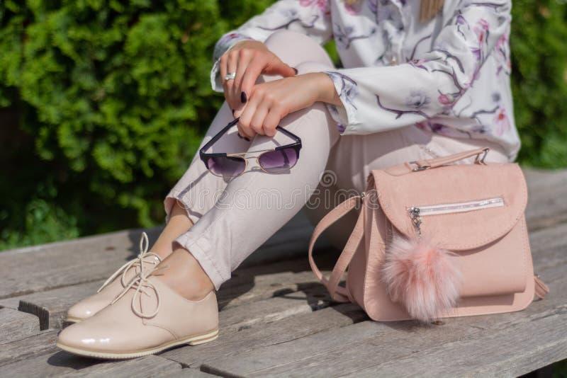 Mujer con las gafas de sol en las manos que se sientan en un banco al lado de bolso rosado en un parque fotos de archivo libres de regalías