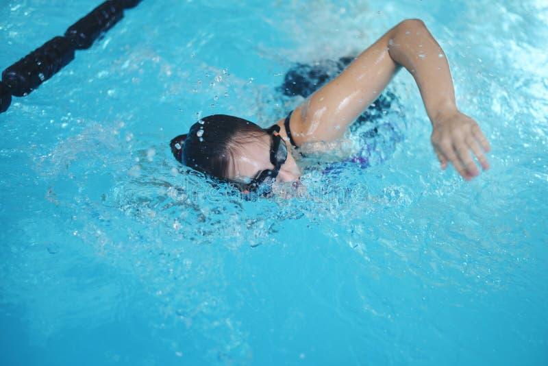 Mujer con las gafas que nada en la piscina de agua foto de archivo libre de regalías