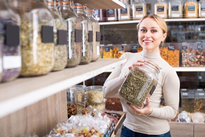 Mujer con las hierbas secadas en tienda orgánica fotos de archivo libres de regalías