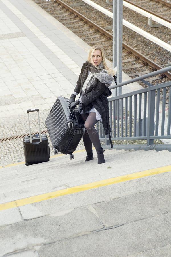 Mujer con las maletas pesadas que camina encima de las escaleras en la estación de tren imágenes de archivo libres de regalías