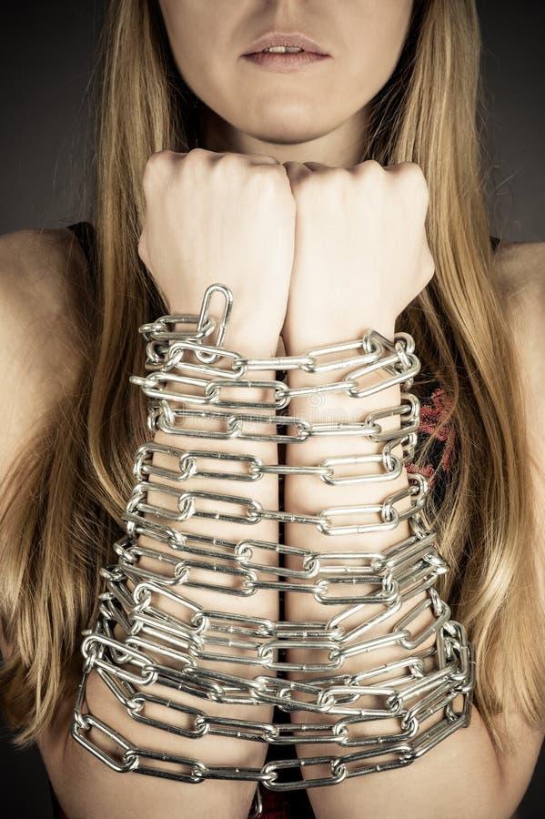 Mujer con las manos encadenadas imagen de archivo