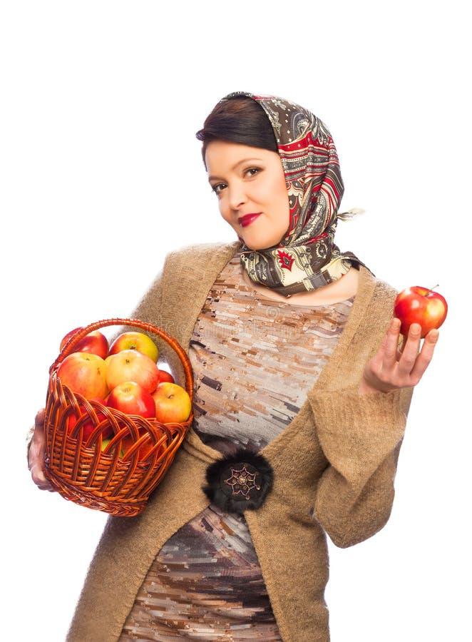 Mujer con las manzanas del otoño en cesta imagen de archivo