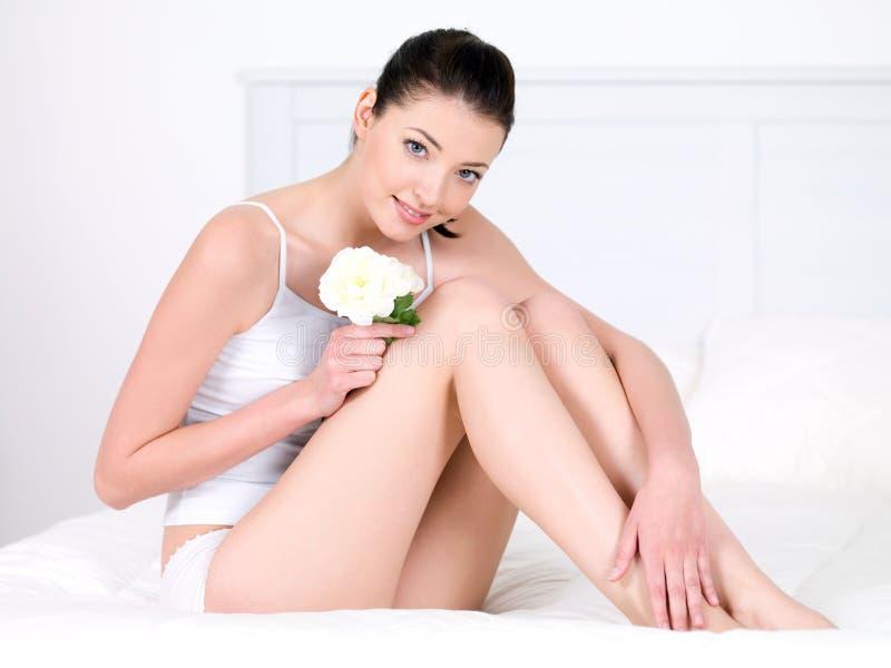 Mujer con las piernas atractivas que se sientan con la flor imagenes de archivo