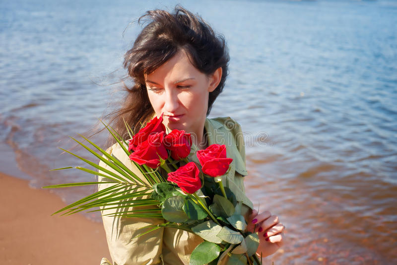 Mujer con las rosas rojas contra el mar en el día soleado imagen de archivo
