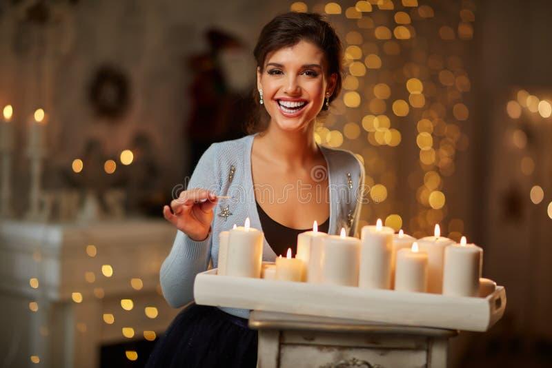 Mujer con las velas, chimenea, luces de la Navidad fotografía de archivo libre de regalías