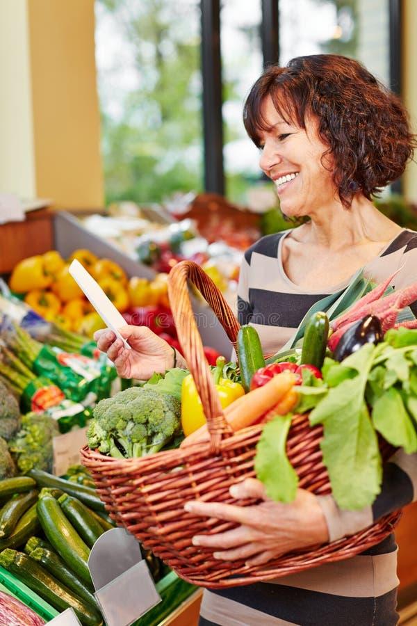 Mujer con las verduras de compra de la lista de compras fotografía de archivo libre de regalías