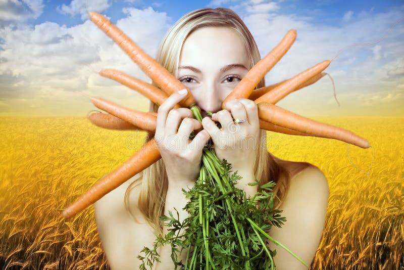Mujer con las zanahorias fotografía de archivo